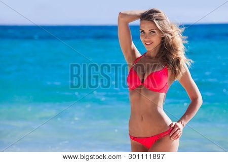 Pretty smiling girl in bikini at tropical sea beach