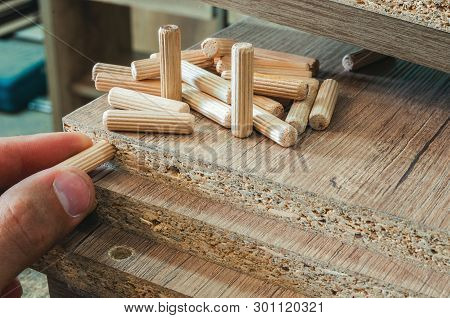 Furniture fittings, wooden dowels, fastener connection on chipboard workpieces, close-up poster