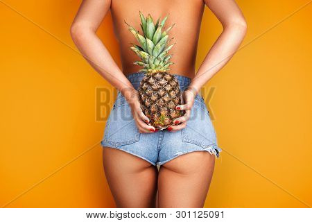 Young Woman Holding A Pineapple In Her Hand.