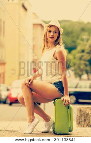 Hitch Hiking And Travelling. Lovely Smiling Cute Girl Sits On Green Suitcase Luggage Baggage Waiting