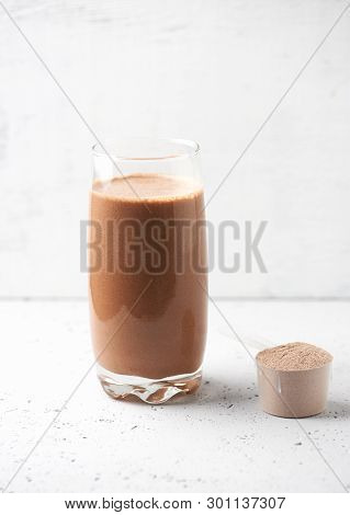 Glass Of Chocolate Protein Shake With Milk And Banana And Whey Protein In Scoop. Sport Nutrition. Br