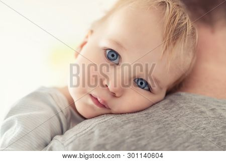 Close-up Portrait Of Cute Adorable Blond Caucasian Toddler Boy On Fathers Shoulder Indoors. Sweet Li