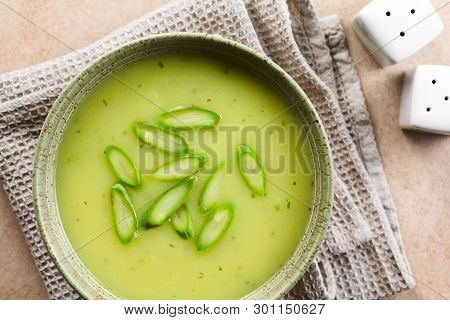 Cream Of Green Asparagus Soup In Bowl, Garnished With Sliced Asparagus On Top, Photographed Overhead