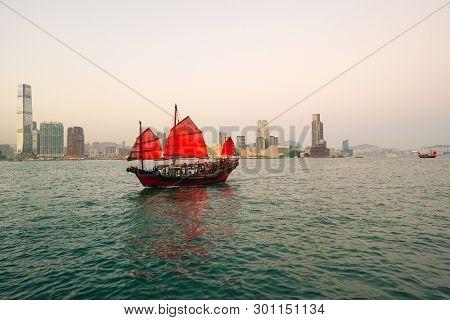 Hong Kong - March 12, 2018: Hong Kong Skyline, With Chinese Junk Boat Sailing Around Victoria Harbou
