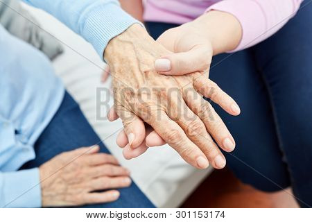 Female nursing assistant or nurse consolingly holds the hand of an old woman
