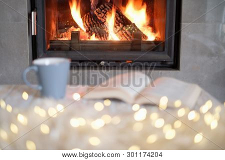 Open book, cup of tea and luminous garland near burning fireplace. Hygge concept
