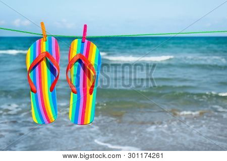 closeup of a pairs of colorful flip-flops, patterned with the colors of the rainbow flag, hanging on a clothes line on the beach, with the sea in the background and a blank space on the right