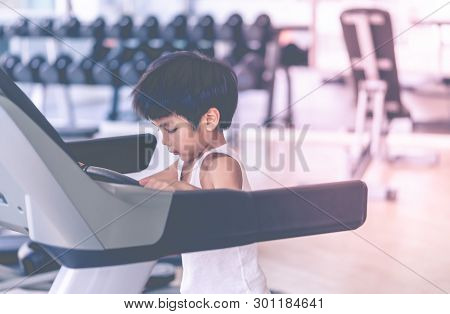 Asian Child Is Running On Treadmill In Fitness Gym