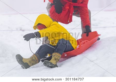 Father Is Helping Her Daughter To Ride The Snow Sled