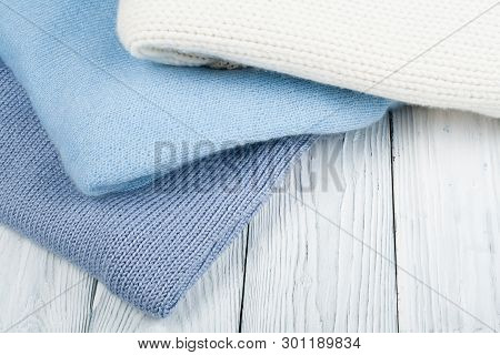 Knitted wool sweaters. Pile of knitted winter clothes on wooden background, sweaters, knitwear, space for text. poster