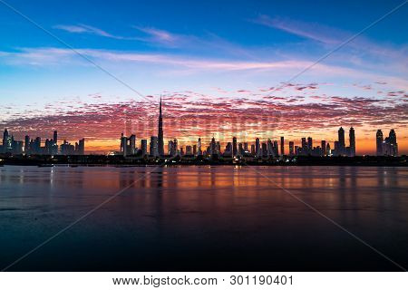 Morning Or Sunrise, Dawn In Dubai. Beautiful Colored Cloudy Sky Over Downtown Dubai. Glow Over Skysc