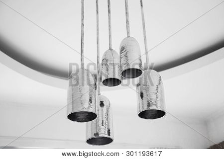 A Group Of Mettalic Hanging Lights On White Ceiling In Loft Designed Appartment. Interior Design Con