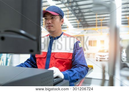 Closed Up Asian Man Mechanic In Uniform Of An Auto Wheel : Computer Wheel Alignment. Balancing Tire