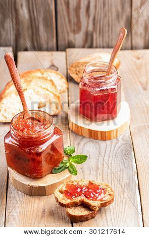 Two Glass Jars Of Strawberry And Apple Jam With Spoons And Sliced Bread On Wooden Table.