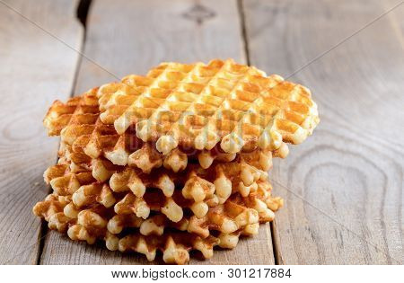 Vertical Stack Of Round Wafers On Wooden Table.