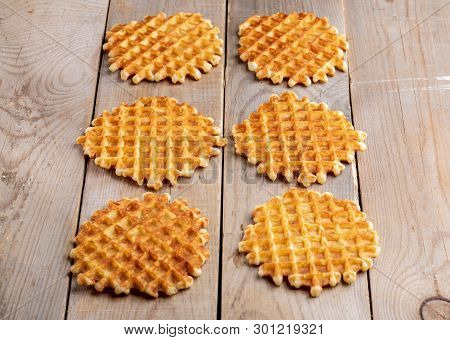 Six Fresh Baked Round Waffles Laid Out On Rustic Wooden Table.