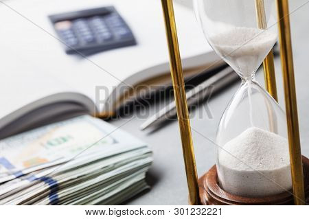Dollar Bills, Hourglass And Notebook For Planning Investments Or Cash Expenses.