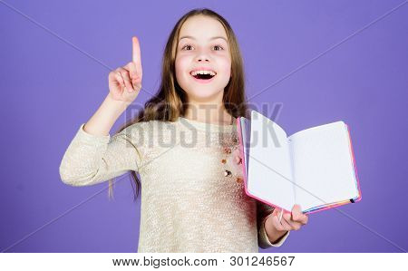 Got Great Idea. Happy Little Girl Holding Open Idea Book And Keeping Finger Raised. Smiling Small Ch