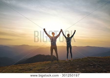 Silhouette Of Man And Woman Standing On Edge Of Mountain And Holding Hands Up On Sunset Sky And Moun