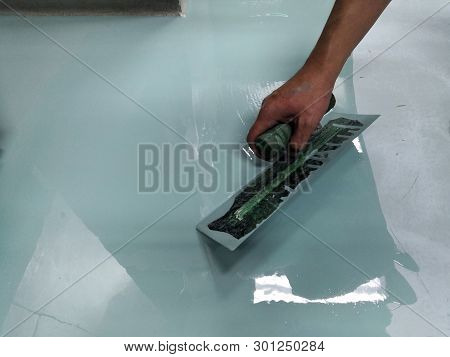 Construction Workers Are Painting The Floor Using The Method Self-leveling Epoxy.spreading Self Leve