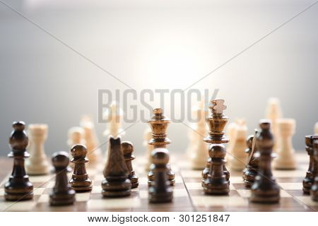 Face To Face Of Wooden Black And White Chess On Chess Board With Sunlight. Battle In Game And Busine