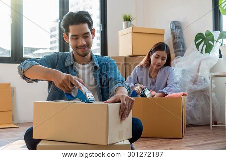 Asian Young Couple Packing Big Cardboard Box For Moving In New Home, Moving And House Hunting Concep