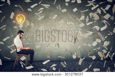 Young Man With Bright Ideas Using A Laptop Building Online Business Earning Money Sitting Under Doll