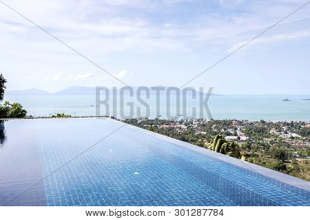 Infinity  Swimming Pool View On Mountain With Clouds And Blue Sky