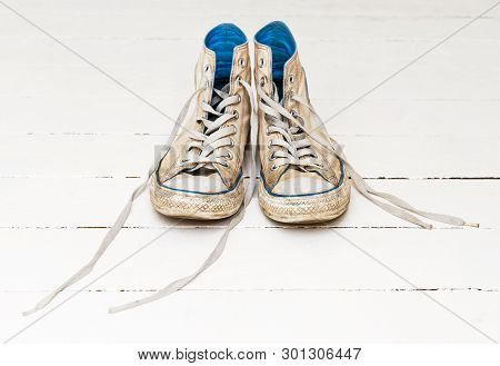 Two Sneakers On The White Wooden Floor