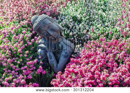 Peaceful Garden. Traditional Serene Buddha Statue Ornament With Beautiful Flowers. Mindful Serenity