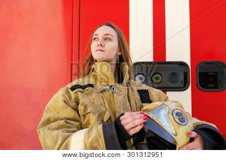 Photo of girl fire looking on side of standing at fire truck