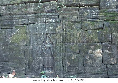 Antique stonework decorated with bas-relief. Stone carving. Ancient ruins overgrown with moss. poster