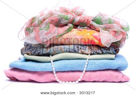 Stacks Of Women Colored Clothes On White Background