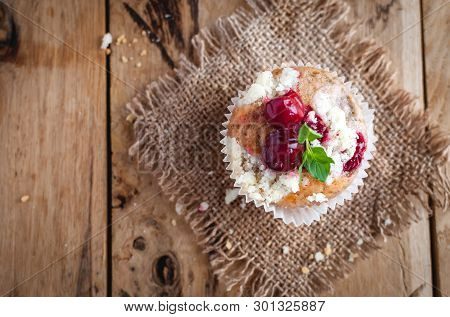 Close-up Of Cherry Muffin With Crumbly Topping On Wooden Background, Top View
