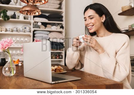 Smiling young woman having breakfast while sitting at the kitchen and using laptop computer
