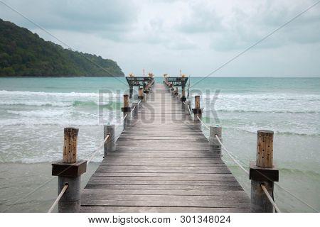 Wood Bridge On Beach. Pier Beach, Cloudy Sky With Copy Space.