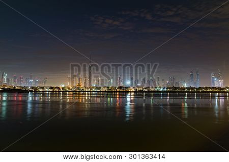 Night Or Dusk In Uae. Morning Or Sunrise, Dawn Over Dubai Downtown. View From Sea To Nightly Dubai Q