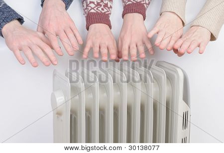 Family warm up hands over electric heater poster
