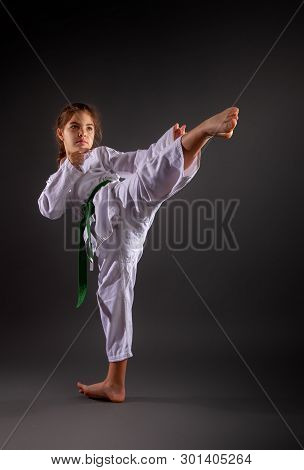 A Little Girl In A Traditional White Kimono For Karate And A Green Belt Performs Training Exercises