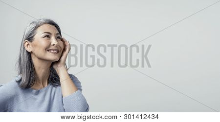 Charming Asian Woman Touches Her Cheek With Hand And Smiles While Looking Up. Portrait Of Smiling Mi