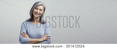 Portrait Of Happy Woman With Broad Smile And Crossed Arms. Cute Asian Grey-haired Woman Broadly Smil