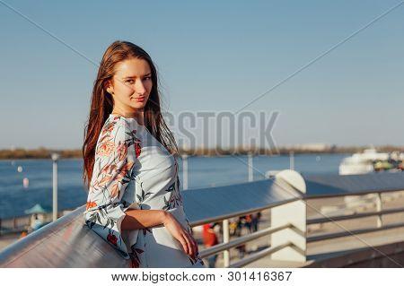 Outdoor Photo Of A Romantic European Woman With Long Hair Spending Time Outdoors Exploring A Europea