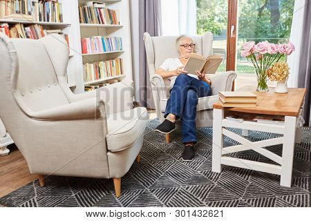 Senior woman reading concentrated in a book in a chair in the senior residence