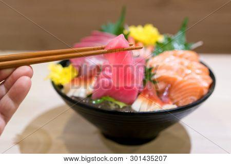 Chopsticks With Tuna Sashimi With Mixed Sliced Fish Sashimi On Ice In Black Bowl. Sashimi Salmon Tun
