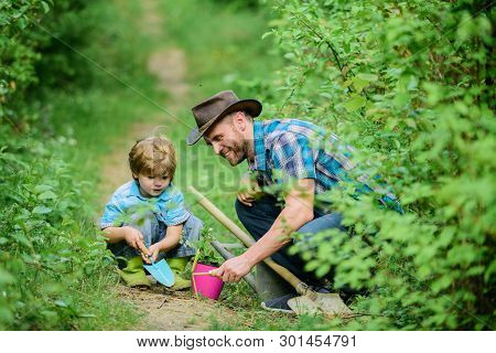 Little Helper In Garden. Farm Family. Little Boy And Father In Nature Background. Gardening Tools. G