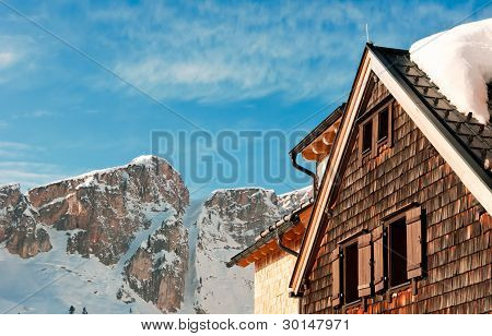 Alpine Hut In Front Of A Mountain Peak In Winter