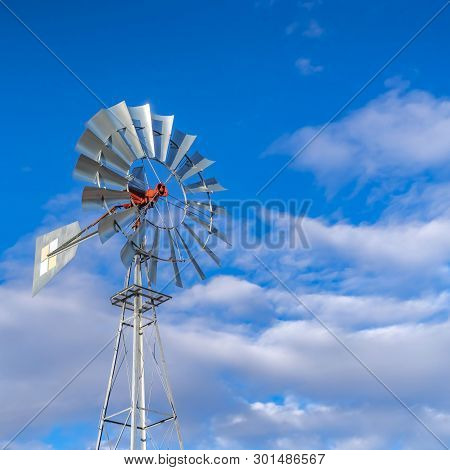 Clear Square Shiny Steel Windpump Against A Vibrant Blue Sky With Cottony Clouds
