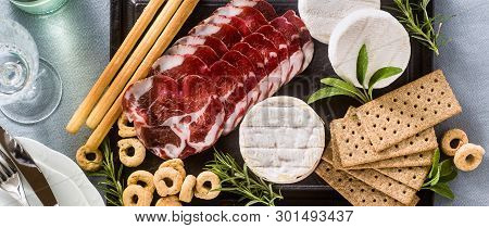 Banner Of Cold Cuts And Cheese Are Served On A Tray On A Table With White Wine, Crackers, Grissini A