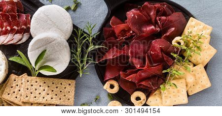 Banner Of Italian Bresaola Served Sliced On A Tray On A Table With White Wine, Crackers, Grissini An