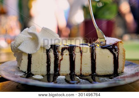 Delicious Gourmet Cheesecake Dripping With Chocolate Sauce And A Dollop Of Whipped Cream On A Beauti